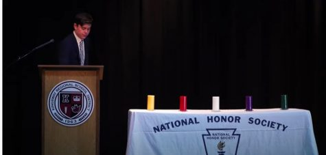 Senior and  NHS Treasurer  Dalton Britner prepares to light the candle for character at the virtual induction ceremony